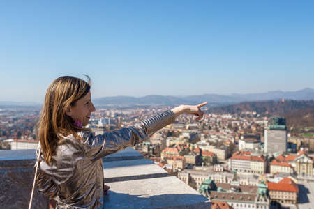 Young woman on top of Ljubljana castle tower pointing to an attraction of the capital city of Slovenia. Archivio Fotografico - 126278877