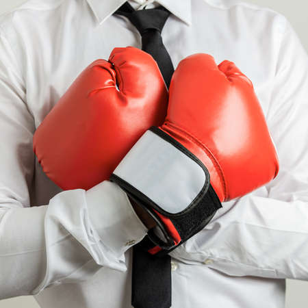 Closeup view of businessman wearing red boxing gloves with his arms crossed on his chest.