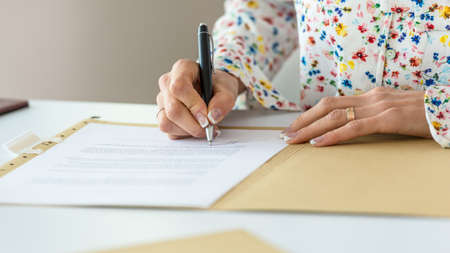 Closeup of businesswoman with perfect french manicure signing a contract or document in a folder. Archivio Fotografico - 126278930