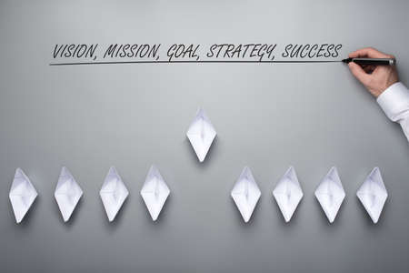 Fleet of paper made origami boats with a Vision, mission, goal, strategy and success sign above them. Over grey background. Stock Photo