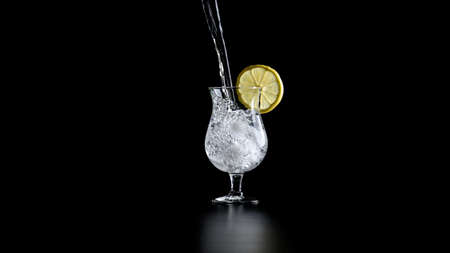 Water pouring in a cocktail glass with lemon rind on the edge. Over black background.