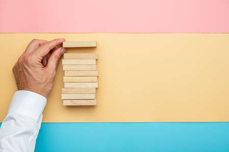 Top view of male hand making a stack of wooden blocks over a background of pink, yellow and blue paper.