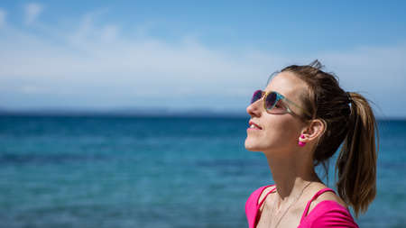 Young woman with colorful sunglasses standing by the sea enjoying the sunny day. Archivio Fotografico - 126278938