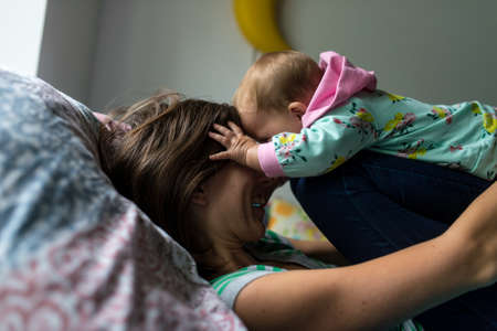 Cheerful young mother lying on her bed with her baby daughter lovingly playing with her. Stockfoto