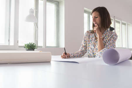 Young woman sitting in an office working on a project with rolled up designs or blueprints on her desk.