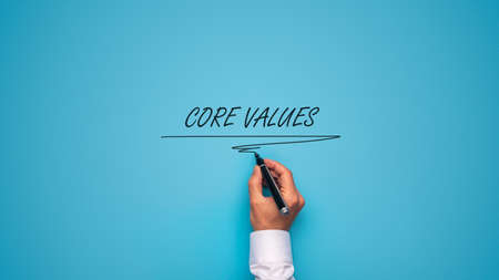 Male hand writing Core values sign over blue background with black marker.