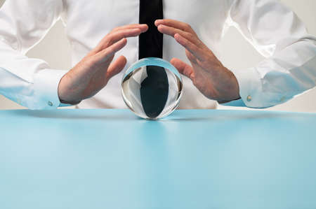 Front view of a man holding protective hands over a crystal sphere in a conceptual image.