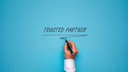 Male hand writing a Trusted partner sign with black marker over blue background.
