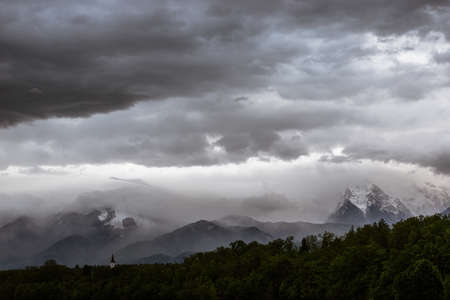 Cloudy overcast over a beautiful view of mountains and a church in a forest. Archivio Fotografico - 126278986
