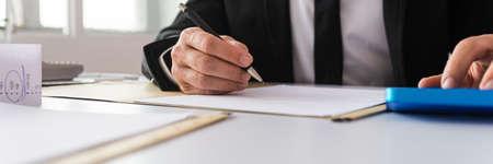 Imagen de vista amplia del empresario trabajando en trámites financieros con calculadora. Con papeles y rollo de recibos en su escritorio.