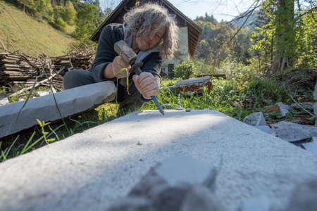 Low angle view of a senior artist carving stone with mallet and a chisel outside in nature with old house in background.