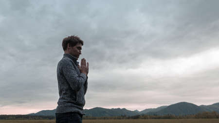 Young man standing in nature with his hands joined together on his chest as he meditates under cloudy sky. Stock fotó - 128872623