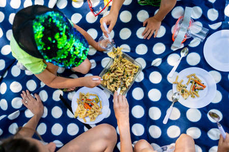 Overhead view of a family having picnic eating pasta on a polka dot blanket.