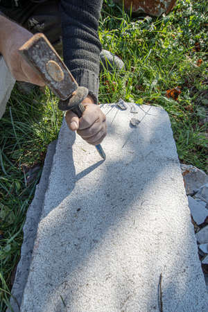Top view of an artist carving in stone using mallet and a chisel.
