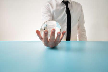 Vue de face d'un homme en chemise élégante et cravate tenant une sphère de cristal dans sa main devant lui dans une image conceptuelle.