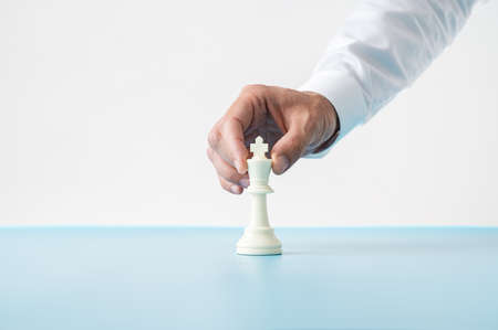 Hand of a businessman placing white chess figure of king on blue desk.
