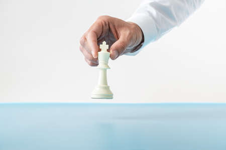 Hand of a businessman about to place a king chess figure on a blue desk in a conceptual image. Over white background. Imagens