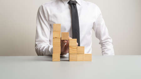 Conceptual image with businessman supporting one step in a staircase made of wooden blocks with his finger.