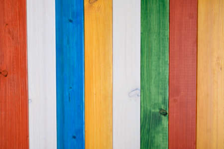 Blurred background of colourful wooden planks coloured red, white, blue, yellow and green. Stock Photo