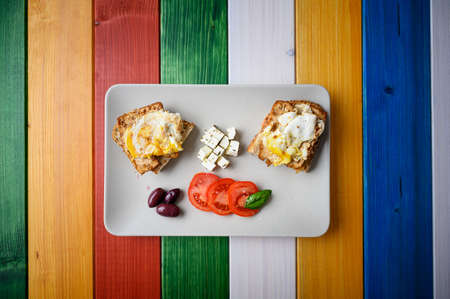 Top view of a plate with egg sandwiches, cheese, olives and tomatoes on a colourful wooden planks. Banco de Imagens