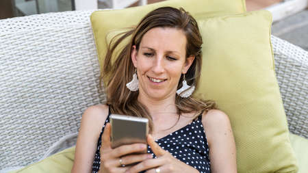 Cheerful young woman with a smile on her face relaxing on patio furniture browsing one her smart phone.