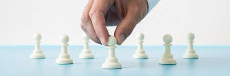 Wide view image of male hand holding the first of many pawn chess pieces placed on blue desk in a conceptual image. Imagens