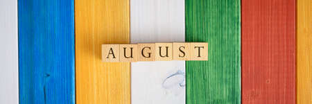 Wide view image of wooden cubes spelling the word August over colourful wooden background. Stock fotó