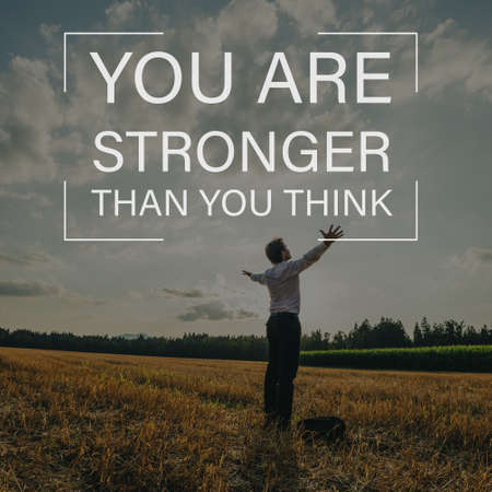 You are stronger than you think sign over a businessman standing in nature with his arms spread widely under evening sky.