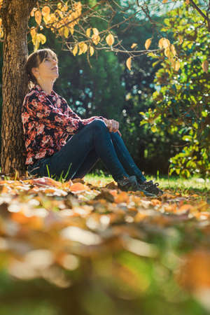 Young woman enjoying under an autumn tree leaning on the tree trunk.
