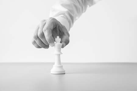 Greyscale image of a businessman placing a king chess figure on a