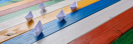 Wide view image of five white paper made origami boats on wooden boards colored in various colors. Imagens