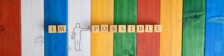 Top view image of a silhouette of a man separating the word Impossible in to the word Possible. Over colored wooden boards.