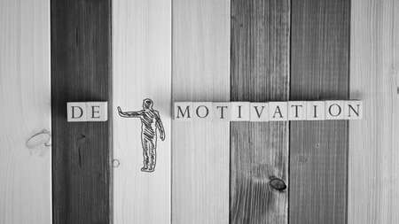 Greyscale image of  hand drawn silhouette of a man pushing away letters DE from the word Demotivation in a conceptual image. Over background of wooden boards.