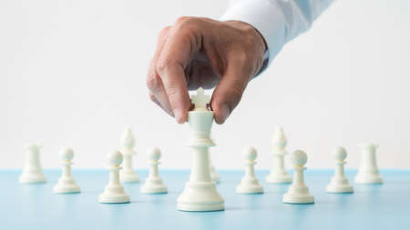 Closeup of male hand holding white chess figure of king positioned in front of the other figures on a blue desk in a conceptual image. Imagens