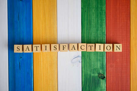 Top view of wooden cubes in a row spelling the word Satisfaction. Over colorful desk of wooden planks.