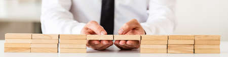 Wide view image of businessman making a connection between two stack of wooden pegs in a conceptual image of business solution or merger.