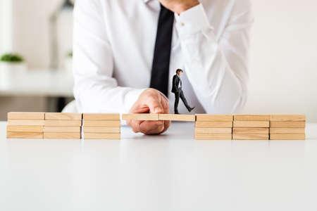 Geschäftsmann, der eine Brücke zwischen zwei Stapeln von Holzpflöcken macht, damit der andere Geschäftsmann hinübergehen kann.