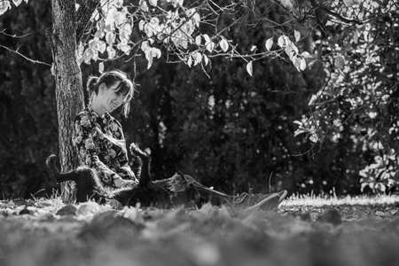 Monochrome image of young woman sitting under an autumn tree lovingly patting her black dog lying on its back in grass.