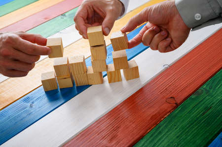 Three hands of businessmen stacking cubes to form a structure in a conceptual image of teamwork. Over colorful wooden background.