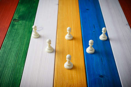 Six white pawn chess pieces placed in a pyramid structure on colorful wooden boards.