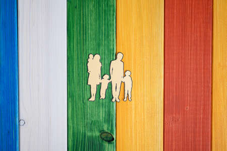 Paper cut silhouette of a family with three children over colorful wooden background.