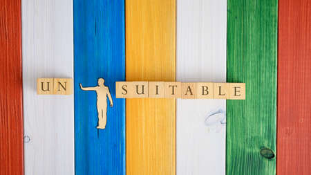 Paper cut silhouette of a man pushing away letters Un from the word Unsuitable spelled on wooden cubes. Over colorful wooden background.
