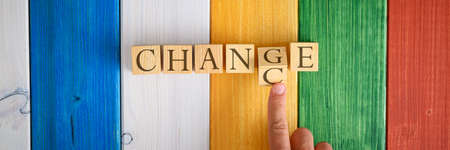 Male hand flipping a wooden cube with letters on it to change the word Chance in to Change in a conceptual image. Over colorful wooden background.