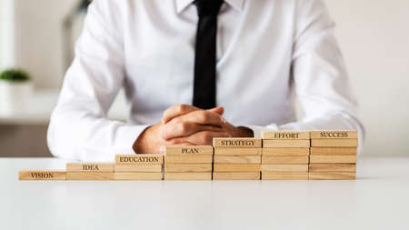 Businessman sitting behind a staircase made of wooden pegs with words Vision, Idea, Education, Plan, Strategy, Effort leading up to Success. Stock Photo