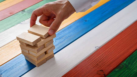 Hand of a businessman building a stack of wooden pegs over colorful background in a conceptual image.