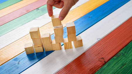 Businessman building a structure of wooden cubes in a conceptual image. On colorful desk of colored wooden boards. Stockfoto