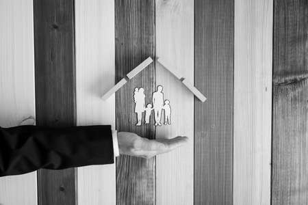 Grayscale image of male hand in a suit under a paper cut silhouette of a family under a roof of wooden pegs in a conceptual image. Over stripped background.