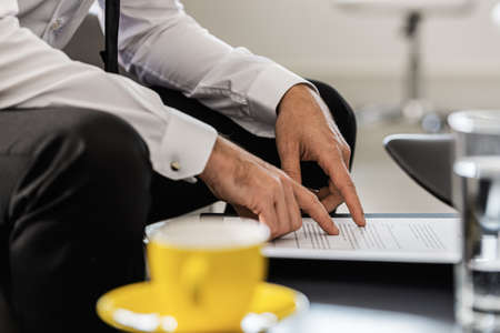 Businessman sitting at an office coffee table proofreading a document or agreement with coffee cup next to him.