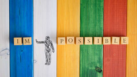 Hand drawn silhouette of a man making a stop gesture to push away letters IM from the word Impossible in a conceptual image. Over colorful wooden background. 版權商用圖片