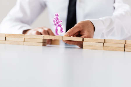 Pink hand drawn silhouette of a man walking across a bridge made between two sides of wooden pegs supported by another businessman. With copy space. Stock Photo